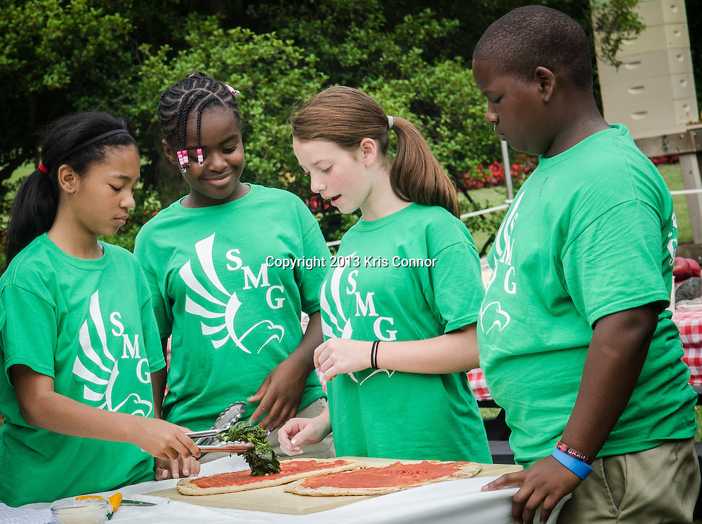 (L-R) Kyla Bourne, Eliza Croom, Rachel Bradley, and Jalen Hurston of Sarah Moore Greene Magnet Technology Academy School, Knox County, TN  make a pizza during an event where they and the First Lady Michelle Obama harvested vegetables from the White House Kitchen Garden for the fifth year in a row at the White House on May 28, 2013 in Washington DC. Photo by Kris Connor
