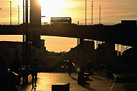 Sunset lights up Glasgow along the River Clyde silhouetting the Kingston Bridge and people walking and exercising in the sunshine