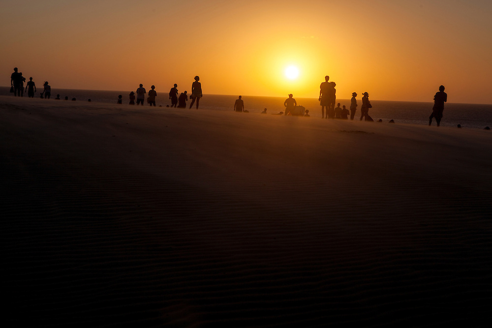 Locals and tourists watching the sun going down at Jericoacoara dunes in Brasil