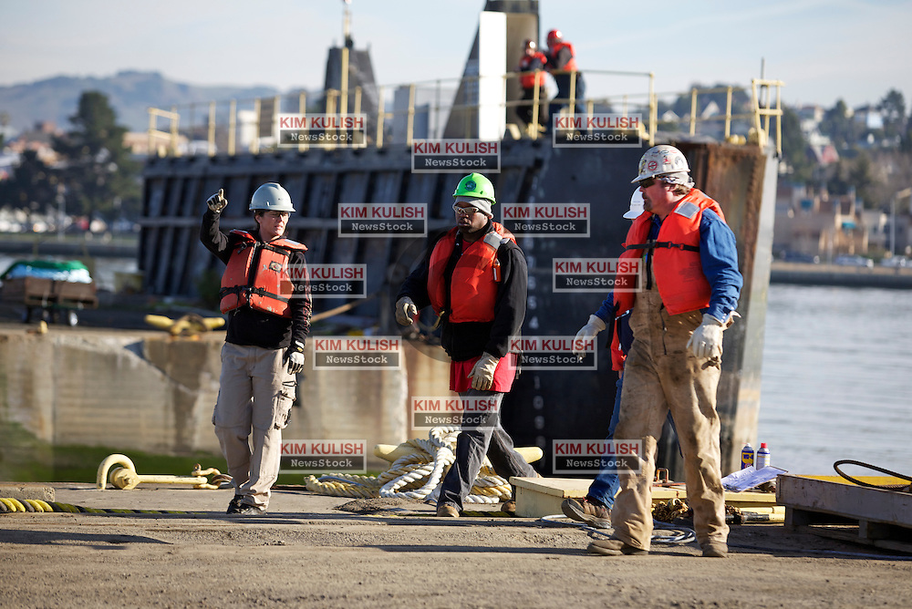 Dock workers wait for the arrival of the Solon Turman,  to the newly re-opened dry docks located on Mare Island in Vallejo, Calif.  California Dry Dock Solutions was recently awarded a $3.1 Million contract from the U.S.Navy to dismantle two ships currently located in Suisun Bay