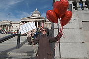 A protestor holds heart baloons as she attends a 'We Do Not Consent' rally at Trafalgar Square, organised by Stop New Normal, to protest against coronavirus restrictions, in London on Saturday, Sept. 26, 2020. (VXP Photo/ Gio Strondl)