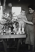 baby standing with mother France Christmas 1955