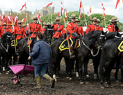 © Licensed to London News Pictures. 11/05/2012. Windsor, UK A girl pushes a wheel barrow past The Royal Canadian Mounted Police, pictured in front of Windsor Castle as they prepare to exercise their horses along the River Thames. The Royal Windsor Horse Show in Windsor, England on May 11 2012. Photo credit : Stephen Simpson/LNP