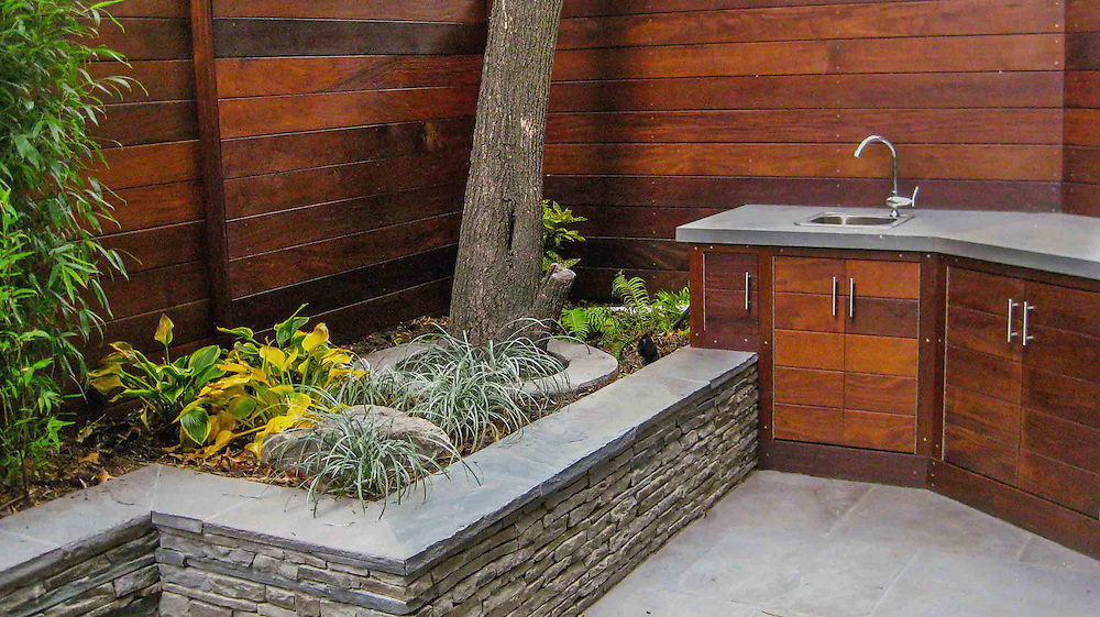 Small city garden with custom stacked stone retaining wall, custom BBQ cabinets, Blue stone paving, Ipe fence and planting
