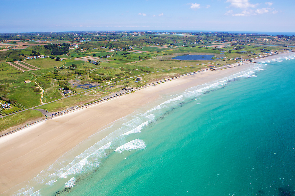 Aerial view of the cystal clear, turquoise water at St Ouen, the five mile road beach, on a sunny summers day in Jersey, Channel Islands