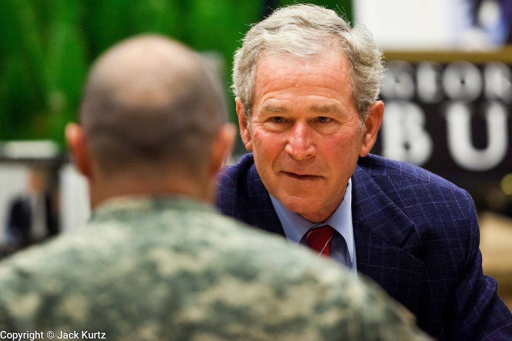"""09 DECEMBER 2010 - PHOENIX, AZ: Former President GEORGE W. BUSH greets American soldiers and signs copies of his book, """"Decision Points"""" at the Barnes & Noble Bookstore in Phoenix, AZ, Thursday, Dec. 9. More than 2,000 people lined up starting at 5AM to get copies of the former President's book, """"Decision Points."""" A handful of protesters demonstrated against President Bush near the bookstore, calling him a """"war criminal.""""  PHOTO BY JACK KURTZ"""