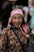 Woman smokes a pipe at the Menghan Sunday market, Xishaungbanna, China.