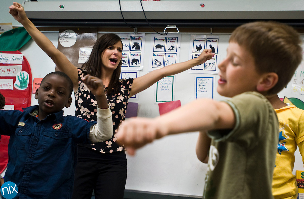 Royal Oaks Elementary teacher Janelle Patterson dances with kindergarten students Da'Marryian Simmons, Isabella Childs and Eithan Nimer in her class at the school Wednesday morning. Patterson was name Cabarrus County Schools Teacher of the Year.  (Photo by James Nix)