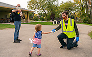 Poll worker Jeffrey Hickel accepts an absentee ballot from 2-year-old Zoe Schabow as her father Adam Schabow documents turning in his ballot at Tenney Park during the Democracy in the Park event Sept. 26th. (Photo © Andy Manis)