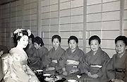 Miko posing with Japanese tourists in an traditional Onsen hotel 1950s 1960s
