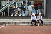 An older Japanese couple sitting in the street outside a clothes shop in Jinbocho, Tokyo, Japan. Friday June 2nd 2017