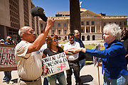09 MAY 2011 - PHOENIX, AZ: MANUEL MARTINEZ, left, an immigrants' rights supporter, and KATHRYN KOBOR argue about illegal immigration at the Arizona State Capitol in Phoenix Monday. Governor Jan Brewer, State Senate President Russell Pearce and Attorney General Tom Horne, all Republicans, held one press conference to announce that the state was suing to take its legal battle over SB1070, Arizona's tough anti-immigration law, past the US Court of Appeals and straight to the US Supreme Court. State Senator Steve Gallardo, a Democrat, held a press conference to announce that he was opposed to the Republican's legal actions and called on them to drop the suit altogether. Isolated shouting matches broke out between activists on both sides of the immigration issue during the press conferences.       Photo by Jack Kurtz