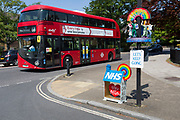 With the promise of the UK government's Corinavirus lockdown being relaxed within a couple of few days, local Fine Art artist Kevin McKeon has added to his existing artwork with another tribute and thanks to NHS (National Health) workers who pass-by this location in Herne Hill in south London, on 7th May 2020, in London, England. Adding to his already popular NHS 'house' on the pavement, McKeon (whose arts practice is normally figurative and heritage carving projects) has created a circular podium attached to a traffic sign pole, of miniature healthcare employees holding placards reading 'Save Lives' and 'Help Us Help You', in the spirit of supporting the NHS during the Covid pandemic. McKeon says the piece was made during his lockdown time at home, shared with a partner who works in Mental Health.