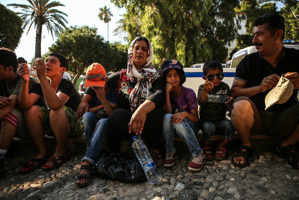 """Salma Abd Alkader, middle, poses for a portrait with her children and husband outside the police station in Kos, Greece as she waits for her name to be called to receive her travel documents on June 29, 2015. The Syrian family paid $2,000 to illegally travel from Bodrum, Turkey to the greek island of Kos in an inflatable dinghy in the darkness of night. Like many migrants and refugees, Abd Alkader fears crossing unknown borders in her journey north into Europe. """"I had fear for this journey. I feared for my children. But now, I feel relaxed because the death stage is finished,"""" said Abd Alkader through a Syrian translator who arrived on the island in the same boat.<br /> <br /> From left to right: Muhammed Abd Alkader, 14; Anas Abd Alkader, 10; Salma Abd Alkader, 35; Rajmd Abd Alkader, 9; Bilal Abd Alkader, 4; and Khattab Abd Alkader, 50."""