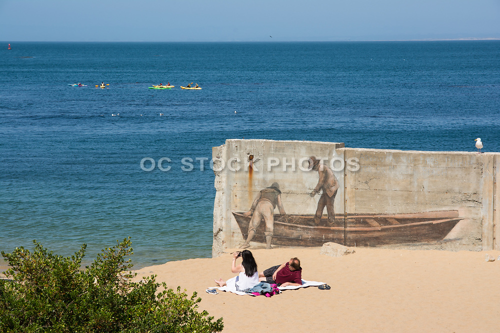Couple Sitting On The Beach By Cannery Row In Monterey