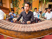 15 MARCH 2015 - SIEM REAP, SIEM REAP, CAMBODIA: A Cambodian musician plays a roneat (Khmer xylophone) at the annual mass merit making at Wat Bo in Siem Reap. More than 1,200 Buddhist monks, from across Siem Reap province, received alms from Buddhist lay people during the morning long ceremony. Wat Bo was originally built to be a the temple for Siamese (Thai) troops when Siem Reap and western Cambodia were controlled by Siam (Thailand). Now Wat Bo is one of the most important temples in Siem Reap.      PHOTO BY JACK KURTZ