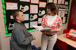 Teacher and pupil talking in a classroom,