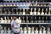 Variety of skin colours and ethnicity on wig model heads in high-street fashion shop window.