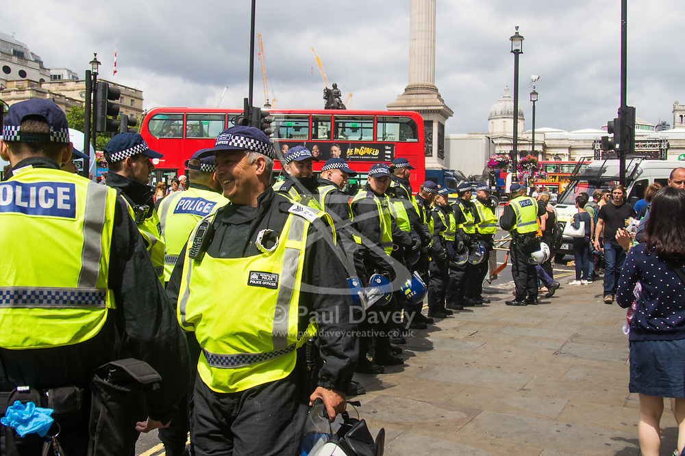 London, June 24th 2017. Anti-fascist protesters counter demonstrate against a march to Parliament by the far right anti-Islamist English Defence League. PICTURED: Riot police form a barrier at Trafalgar Square to separate the two opposing sides.