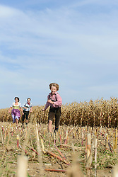 Family running in cornfield, Bavaria, Germany