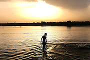 A man is bathing in the polluted Ganges River in Kanpur, Uttar Pradesh, at dawn. Sustaining life for thousands of years along the Indo-Gangetic plains, the river's ecosystem is in grave danger of being damaged beyond repair.