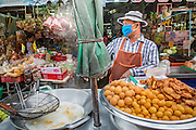 "03 OCTOBER 2012 - BANGKOK, THAILAND:    A fried snack vendor in Khlong Toey Market in Bangkok. Khlong Toey (also called Khlong Toei) Market is one of the largest ""wet markets"" in Thailand. Thousands of people shop in the sprawling market for fresh fruits and vegetables as well meat, fish and poultry every day.    PHOTO BY JACK KURTZ"