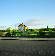 A solitary occupied home standing in wasteland in an undeveloped area of land by the river Mersey in Birkenhead, Wirral. The Mersey is a river in north west England which stretches for 70 miles (112 km) from Stockport, Greater Manchester, ending at Liverpool Bay, Merseyside. For centuries, it formed part of the ancient county divide between Lancashire and Cheshire.