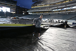 Lincoln Financial Field grounds crew team members remove a tarp that was on the field before the NFL game between the Chicago Bears and the Philadelphia Eagles on Sunday, December 22nd 2013 in Philadelphia. (Photo by Brian Garfinkel)
