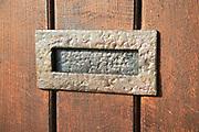 Close up of metal letter box in wooden front door, UK