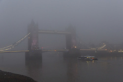 © Licensed to London News Pictures. 30/12/2016. LONDON, UK.  A commuer boat passes under Tower Bridge on the River Thames, which is shrouded in fog. London is experiencing more freezing and foggy weather this morning.  Photo credit: Vickie Flores/LNP