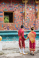 A young Laotian couple poses for engagement photos at Wat Xienghtong in Luang Prabang.