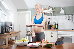 Young woman preparing smoothie in mixer in the kitchen, Bavaria, Germany