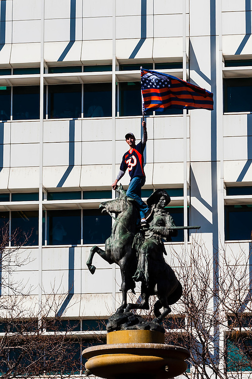A Bronco fan waving an American Bronco flag atop the Pioneer Monument at Broadway and Colfax, Denver Broncos Super Bowl 50 Victory Parade, Downtown Denver, Colorado USA.
