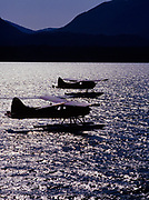 Two de Havilland DHC2 Beavers silhouetted by reflected sunlight while taxiing, Ketchikan, Alaska.