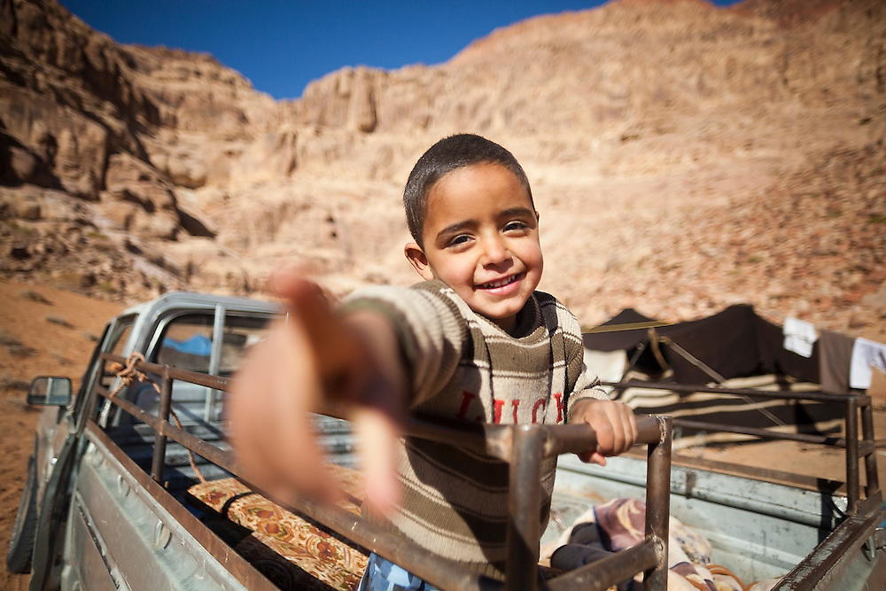 A young Bedouin boy plays in the back of a pickup truck at his family's remote home encampment in Wadi Rum, Jordan.