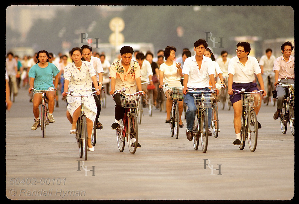 Mass of bicycle commuters pedals past Tiananmen Square in late afternoon sun; Beijing. China