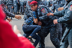 The police violently detain a teenager trying to resist their grip in Republic Square