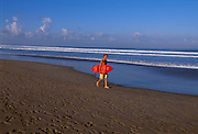 A surfer on the beach in Bali, Indonesia.
