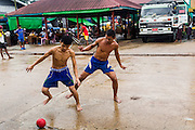 09 JUNE 2014 - YANGON, MYANMAR: Workers play soccer while they wait for a boat to unload on a pier in the San Pya Fish Market (also spelled Sanpya). San Pya Fish Market in Yangon is one of the largest wholesale fish markets in Yangon. The market is busiest in early in the morning, from before dawn until about 10AM.    PHOTO BY JACK KURTZ