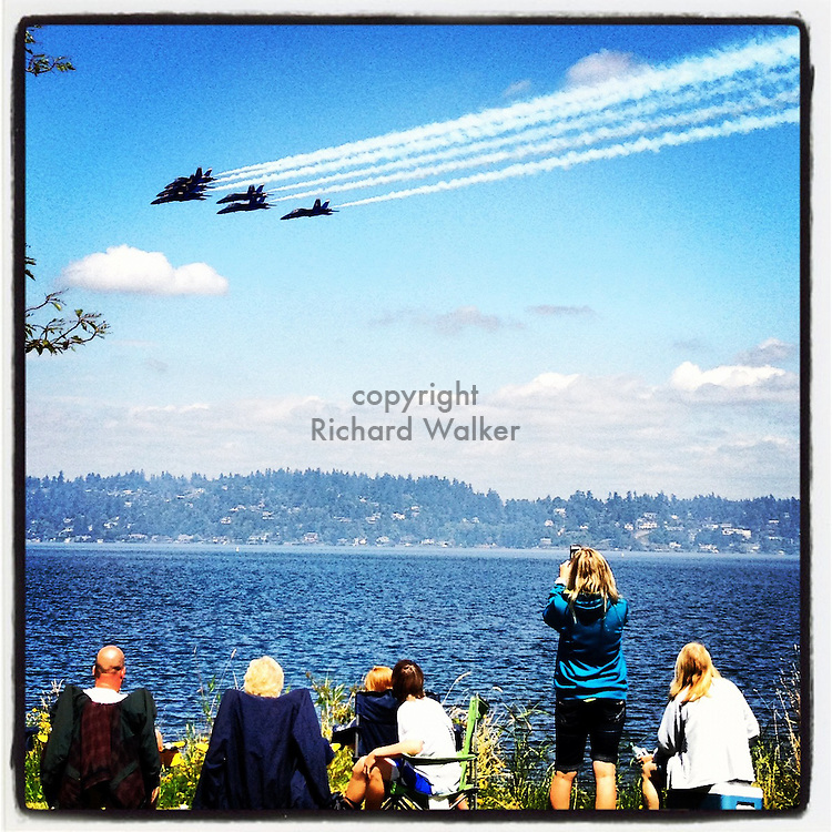 2012 August 02 - Navy Blue Angels fly over Lake Washington, as seen from Seattle, WA, USA, as people watch from shore. In the background is Mercer Island. Taken with Apple iPhone using Instagram App. By Richard Walker