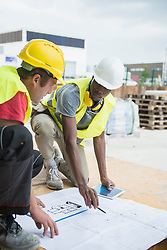 Construction workers reviewing blueprint at construction site, Munich, Bavaria, Germany