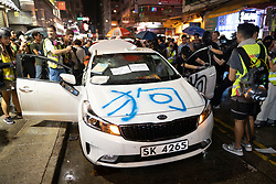 Hong Kong, China. 13th October 2019. Woman suspected of being pro-Beijing is assaulted by pro-democracy protestors in Mongkok district in Kowloon on Sunday evening. This incident was one of several throughout Hong Kong on Sunday which saw acts of vandalism carried out by a minority in the pro-democracy movement. Pic. Unmarked police car is vandalised. Chinese character for dog is sprayed on car. Iain Masterton/Alamy Live News.