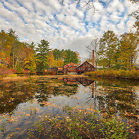 The Daniel Cragin Mill is known today as the Frye's Measure Mill is a historic watermill located in the small New England town of Wilton in Hillsborough County, New Hampshire. This photography image  was taken on an overcast autumn morning when New England fall colors were still eminent. A short break in the sky provided a great mixture of blue sky and puffy clouds.<br />