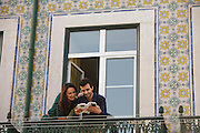 A couple at the balcony of a ceramic tile-decorated facade at Madragoa district in Lisbon