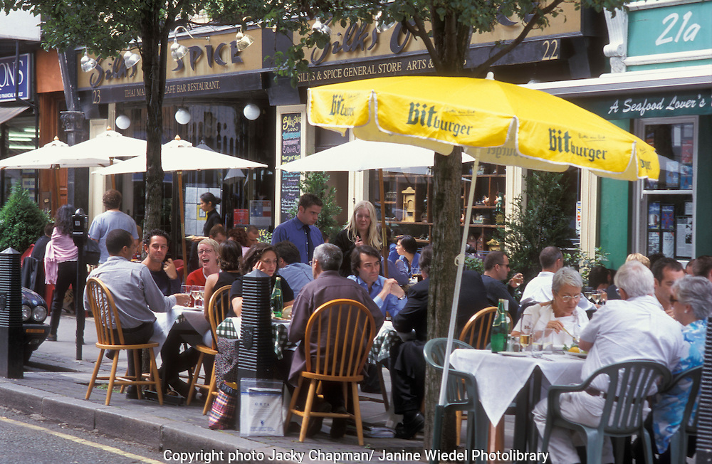 people eating outside on pavement in summer in London.