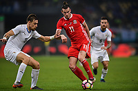 """Gareth Bale, right, of Wales national football team kicks the ball to make a pass against Sebastian Coates of Uruguay national football team in their final match during the 2018 Gree China Cup International Football Championship in Nanning city, south China's Guangxi Zhuang Autonomous Region, 26 March 2018.<br /> <br /> Edinson Cavani's goal in the second half helped Uruguay beat Wales to claim the title of the second edition of China Cup International Football Championship here on Monday (26 March 2018). """"It was a tough match. I'm very satisfied with the result and I think that we can even get better if we didn't suffer from jet lag or injuries. I think the result was very satisfactory,"""" said Uruguay coach Oscar Tabarez. Wales were buoyed by a 6-0 victory over China while Uruguay were fresh from a 2-0 win over the Czech Republic. Uruguay almost took a dream start just 3 minutes into the game as Luis Suarez's shot on Nahitan Nandez cross smacked the upright. Uruguay were dealt a blow on 8 minutes when Jose Gimenez was injured in a challenge and was replaced by Sebastian Coates. Inter Milan's midfielder Matias Vecino of Uruguay also fired at the edge of box from a looped pass but only saw his attempt whistle past the post. Suarez squandered a golden opportunity on 32 minutes when Ashley Williams's wayward backpass sent him clear, but the Barca hitman rattled the woodwork again with goalkeeper Wayne Hennessey well beaten."""