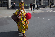 A lady wearing bright African clothing walks across Parliament Square wearing stylish clothing on the occasion of Commonwealth Day, on 11th March 2019, in Westminster, London, England.