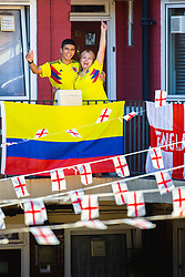 Outnumbered but hoping for victory, A Colombian family and their dog Troy are pictured on the Kirby Estate in Southwark where local residents have put on a huge display of support for England in the World Cup. PICTURED: Son Jean-Paul Jhonnes, 19, and his mother Mother Sandra Ramos, 48, outside their second floor flat . London, July 02 2018.