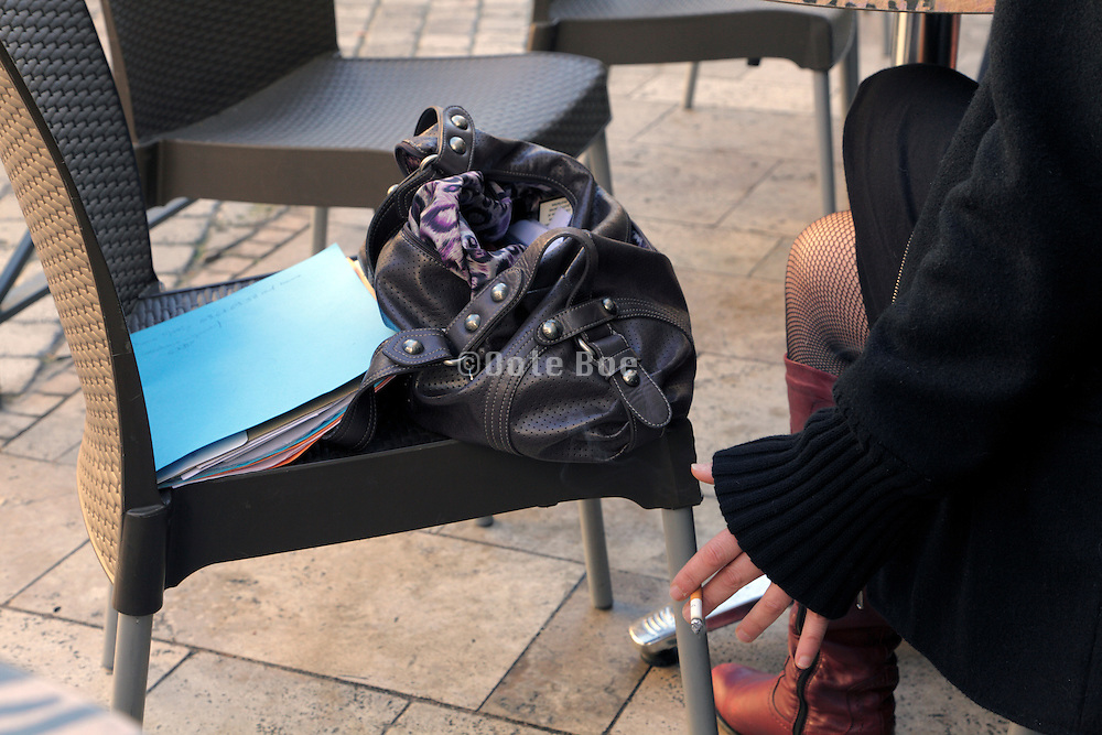 female bag and office papers on a seat outdoors