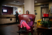 Puerto Rican children wait inside the lobby of the Red Roof Inn as their parents assemble for a vigil outside the hotel, Friday, Jan. 26, 2018, in Hartford, Conn.  Families that have been displaced by Hurricane Maria have been staying at the hotel since November. (Jessica Hill for the New York Times)
